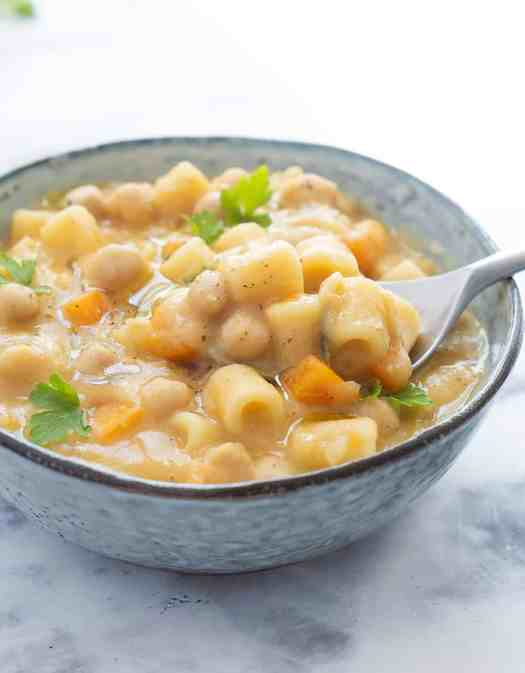 Vegan pasta with chickpeas in a light blue bowl with a spoon - The Clever Meal