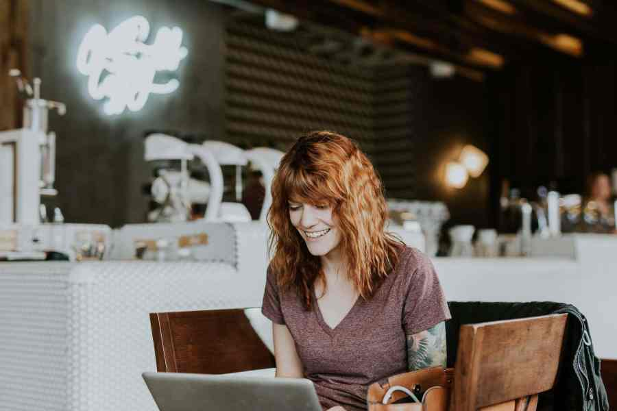 the lady in the coffee shop is laughing while holding her laptop - How Custom Virtual Tours Can Save Your Real Estate Business in 2020