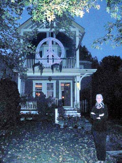 Coaster Photo - Asbury Park resident Linda Myers stands outside her home which features an illuminated peace sign.