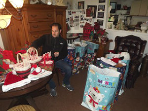 Ross Limo owner Martin Ross packs up holiday gifts and goodies in preparation for Santa to delver them this week to needy Neptune families. Coaster photo.