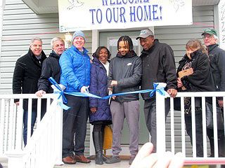 Coaster photo - Christian Cortez, a resident of Meg's Place, cuts the ribbon at the Rights of Passage Home dedication in Asbury Park. From left are: Jim White, Executive Director, Covenant House; Asbury Park Mayor John Moor; President of Covenant House International, Kevin Ryan; Councilwoman Yvonne Clayton; Councilman Jesse Kendle, Youth Specialist at Interfaith Neighbors, Meg Flores and Co-Executive Director of Interfaith Neighbors, Paul McEvily.