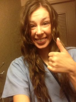Me smiling in my medical gown giving a thumbs up