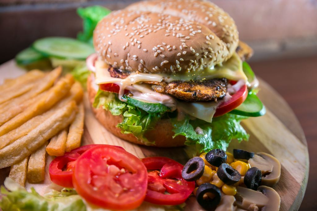 Burger with side of tomatoes, olives, and french fries