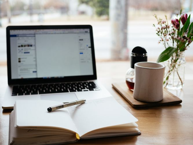 Mug, vase of flowers, journal, pen, and laptop on table in font of a window