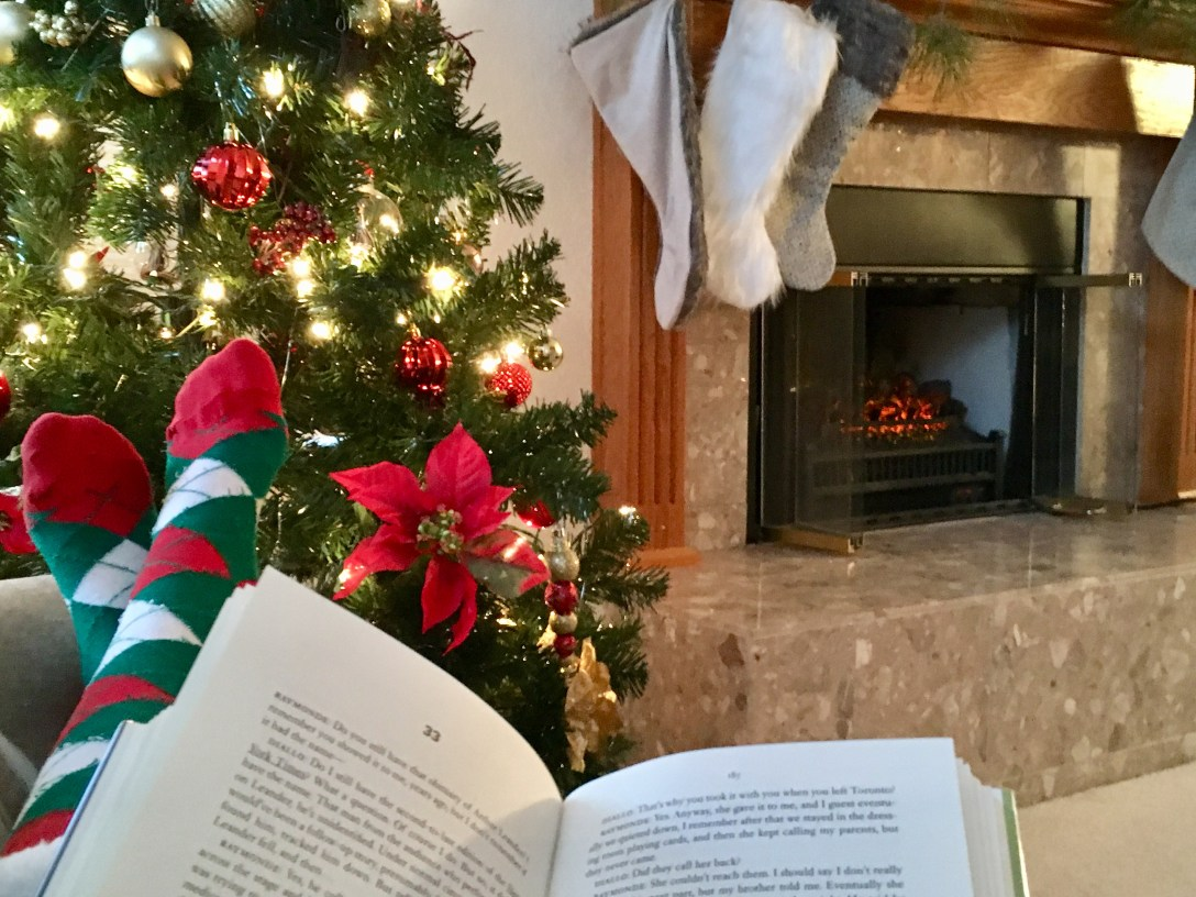 Open book in front of Christmas tree and fireplace