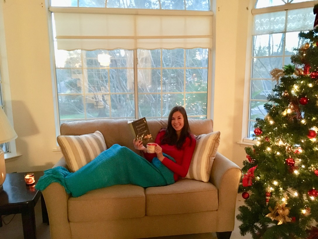 Me sitting on couch with mug and book in a blue blanket