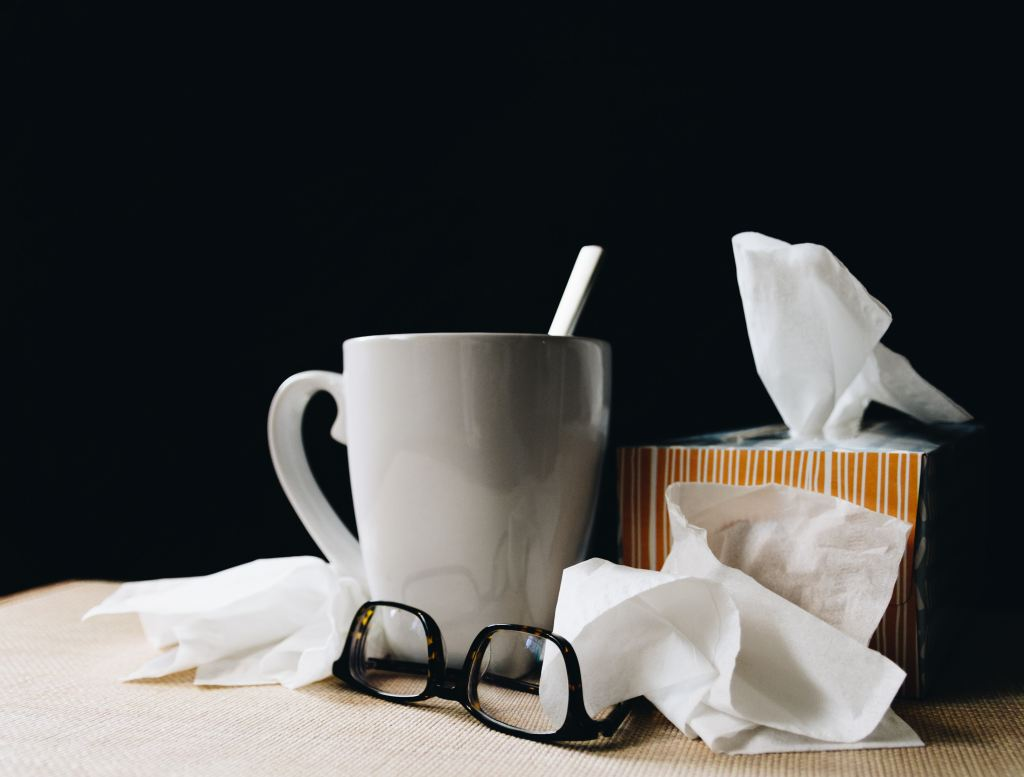 Mug of tea, glasses, tissue box, and used tissues on table