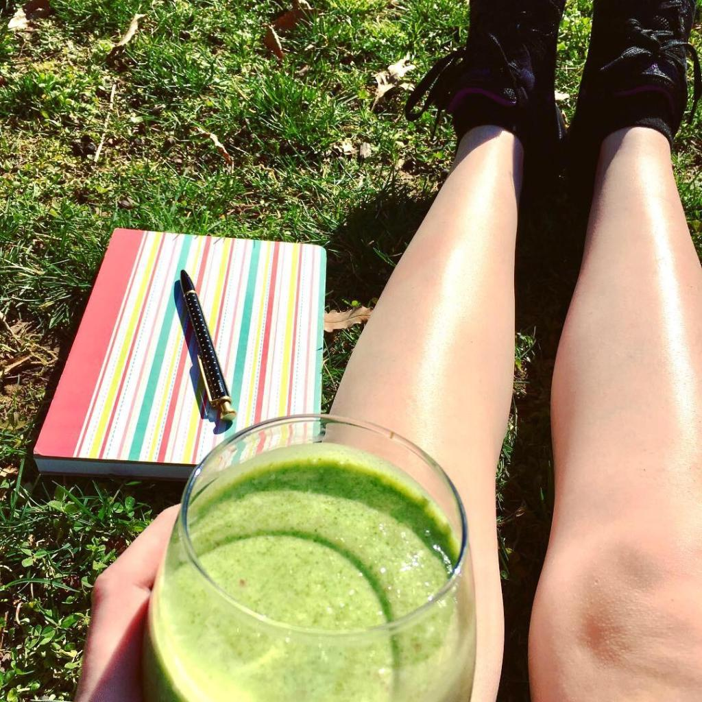Me sitting in grass next to notebook and holding a smoothie