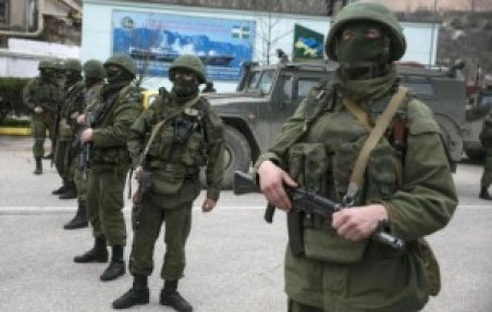Armed servicemen stand near Russian army vehicles outside a Ukrainian border guard post in the Crimean town of Balaclava