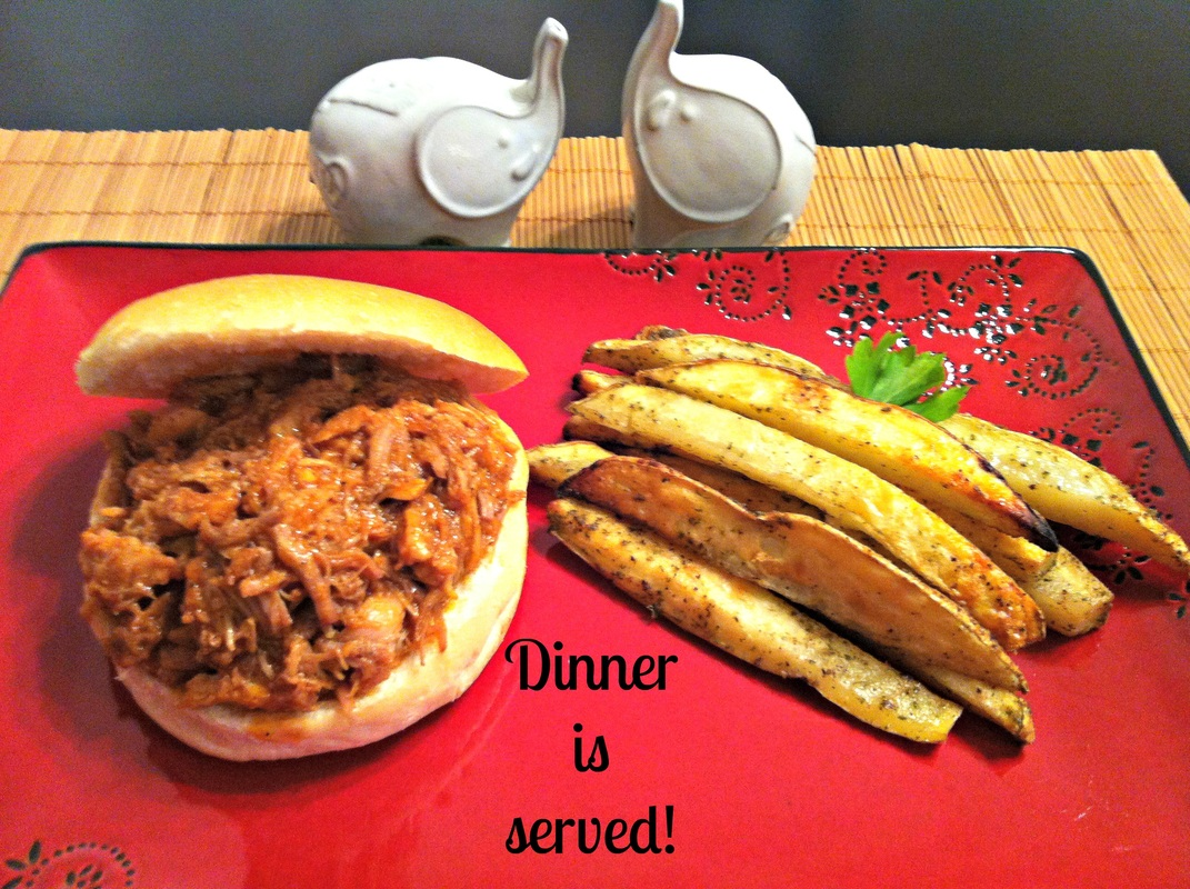 A red plate with homemade potato wedges and a bun filled with pulled pork.