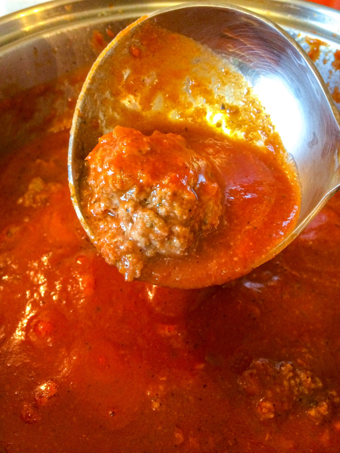 Gently place the raw meatball into the seasoned simmering sauce.