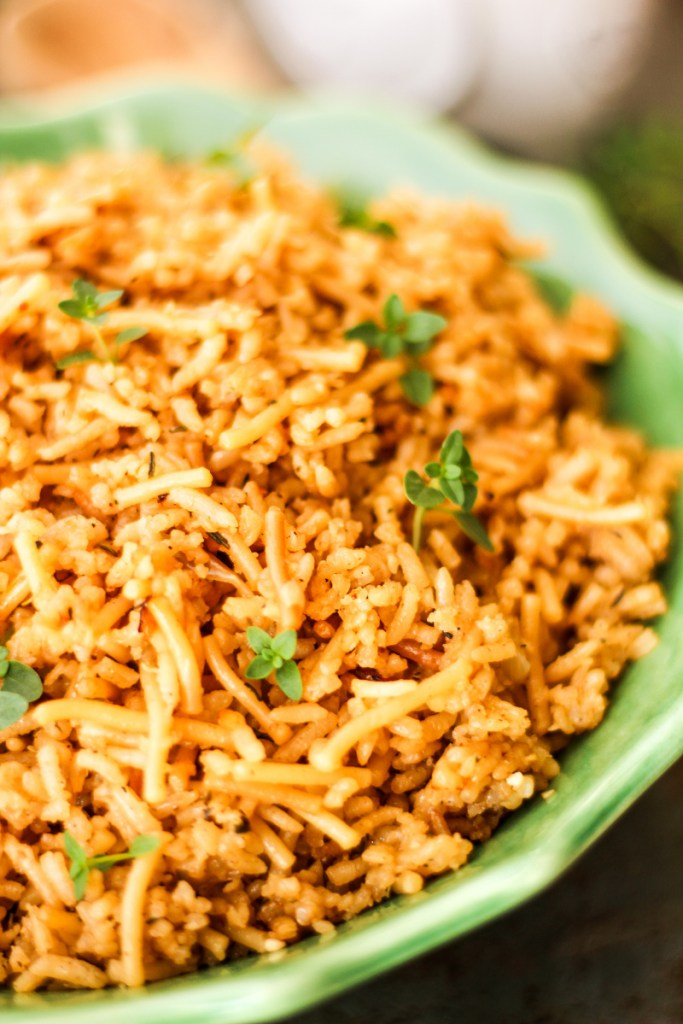 Close up side view of rice pilaf in a green serving bowl.