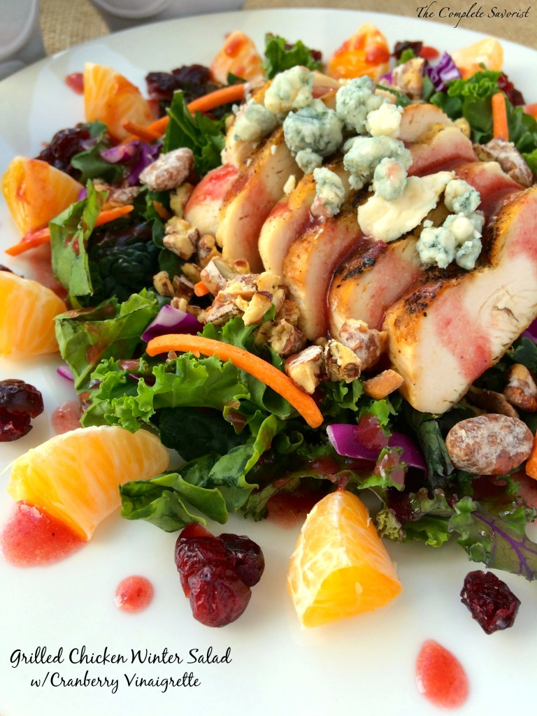 Grilled Chicken Winter Salad with Cranberry Vinaigrette ~ Hearty kale (or mixed greens) loaded with grilled chicken, clementines, dried cranberries, candied pecans, and bleu cheese crumbles in a tangy cranberry vinaigrette ~ The Complete Savorist
