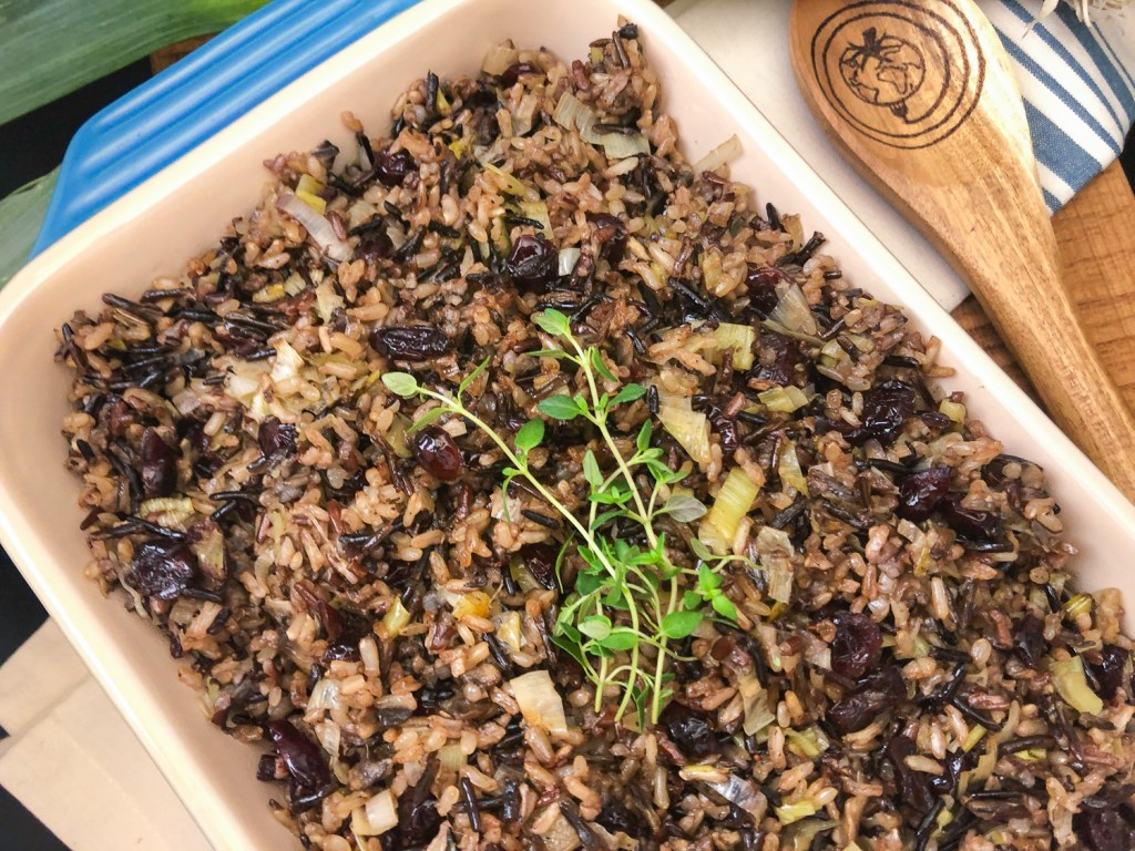 A blue casserole dish full of cranberry leek wild rice garnished with fresh thyme with a wooden spoon with The Complete Savorist logo burned on it.