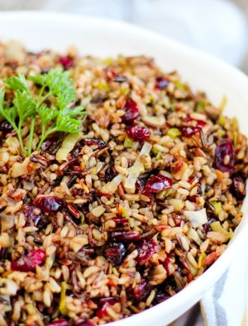 Horizontal shot of cranberry leek wild rice in a white bowl with a dish towel and wooden spoon off to the side