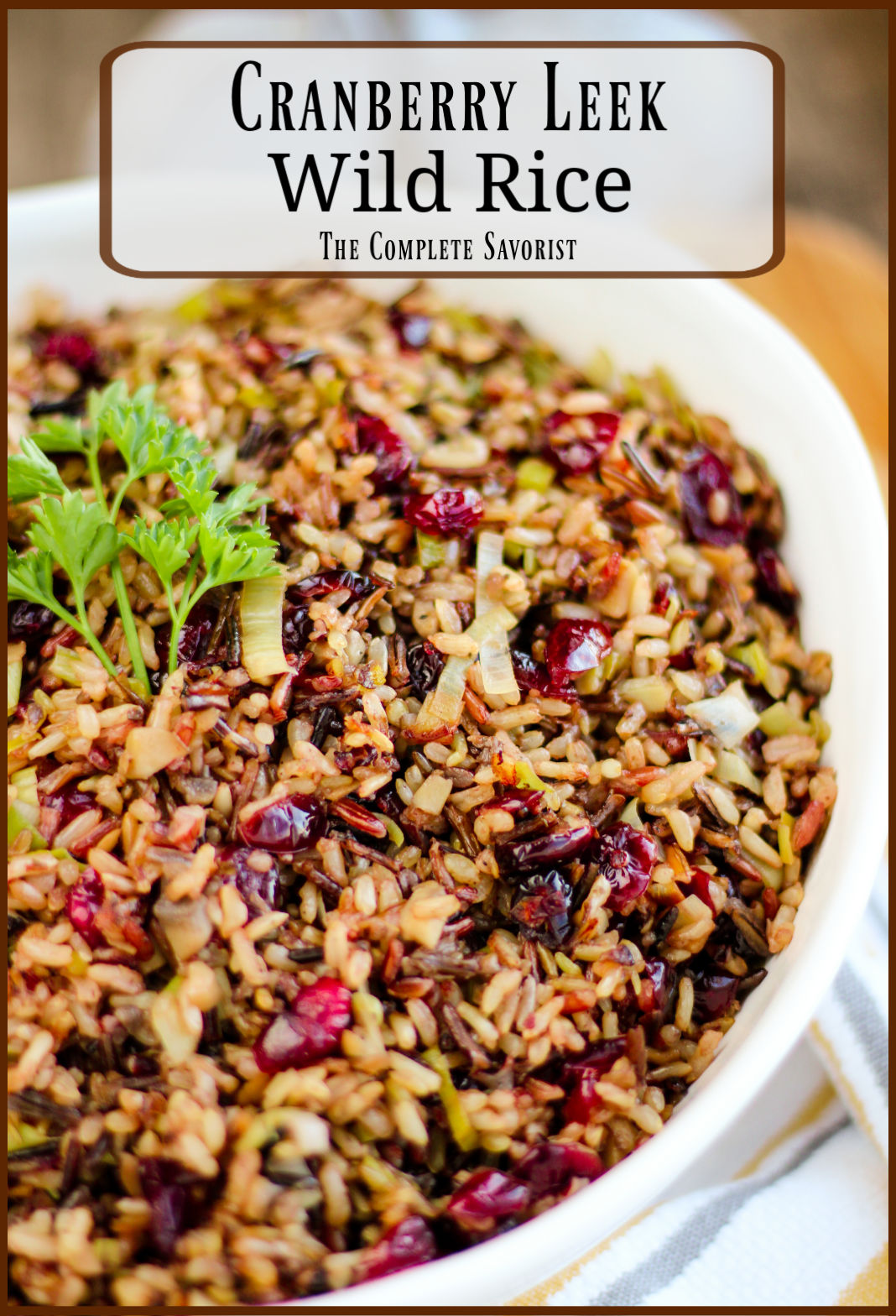 A white serving bowl full of wild rice with cranberries and leeks garnished with a sprig of curly parsley.