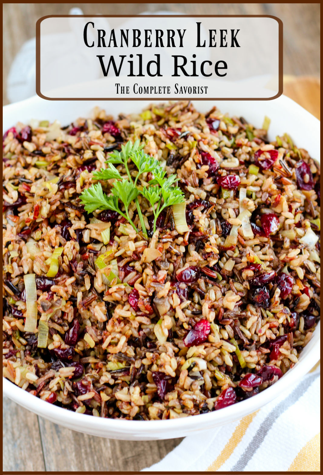White serving bowl filled to the brim with cranberry leek wild rice with curly parsley as a garnish.
