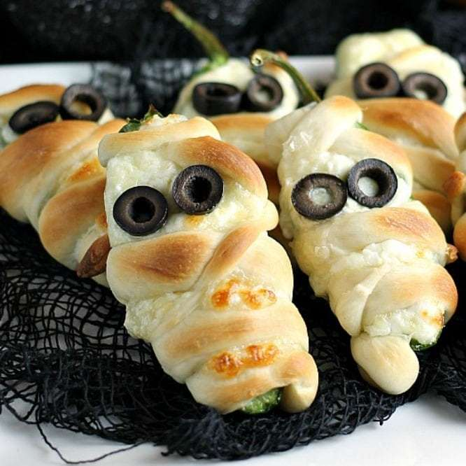 Classical jalapeño poppers wrapped in crescent bread to look like mummies with black olive eyes for Halloween.