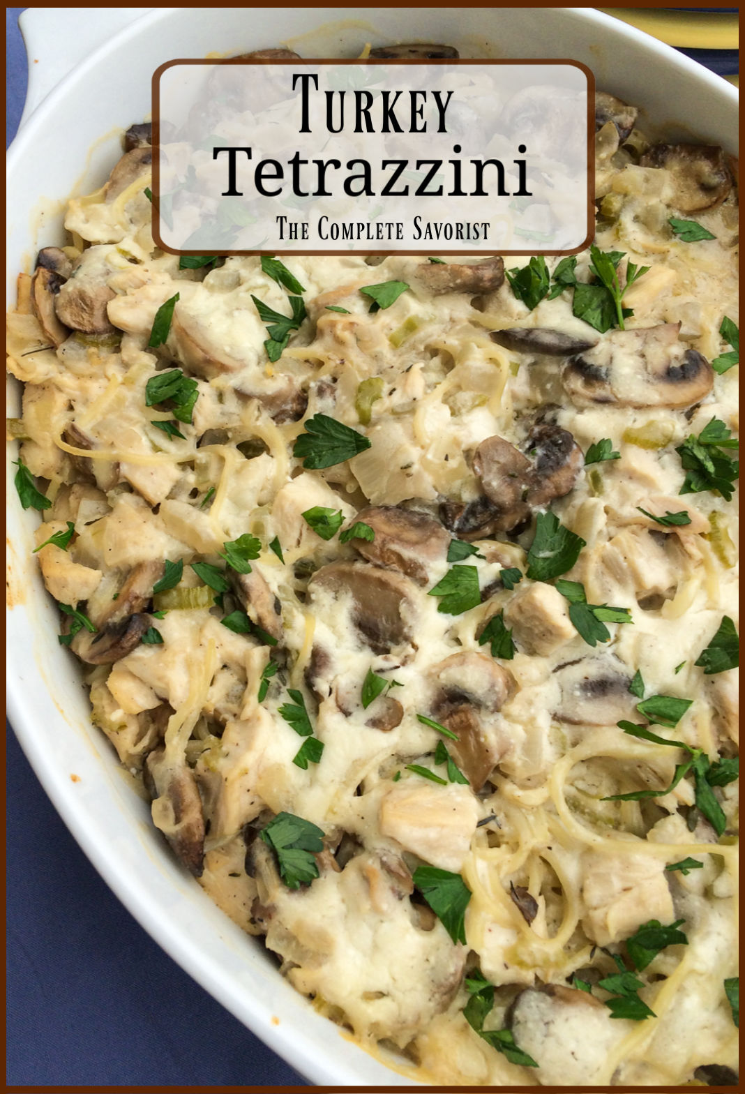 Homemade turkey tetrazzini in a white casserole, baked and garnished with fresh parsley.