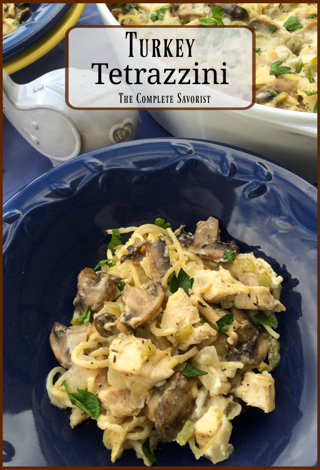 A serving of tetrazzini with mushrooms, turkey, garnished with fresh parsley in a blue bowl with the casserole in the background.
