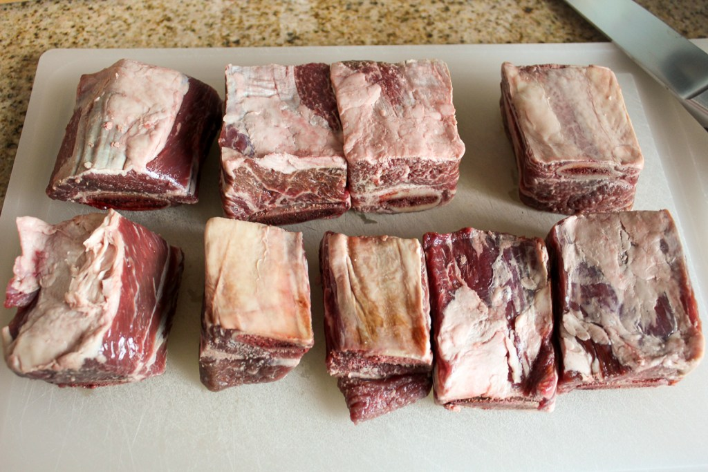 Raw English cut short ribs on a white cutting board.
