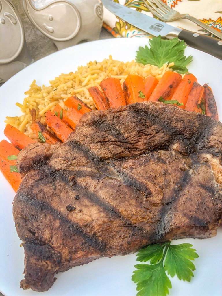 Rice pilaf, seasoned carrots, and a grilled steak on a white plate.