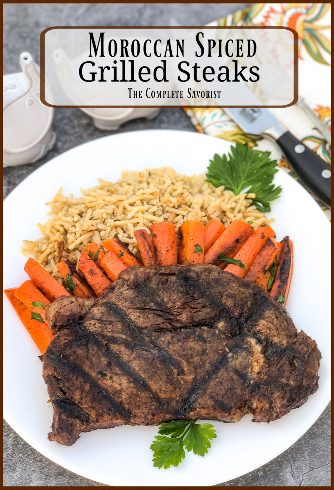 Grilled steak with cooked carrots and rice pilaf on a white plate, garnished with fresh parsley. Knife and fork in the background.