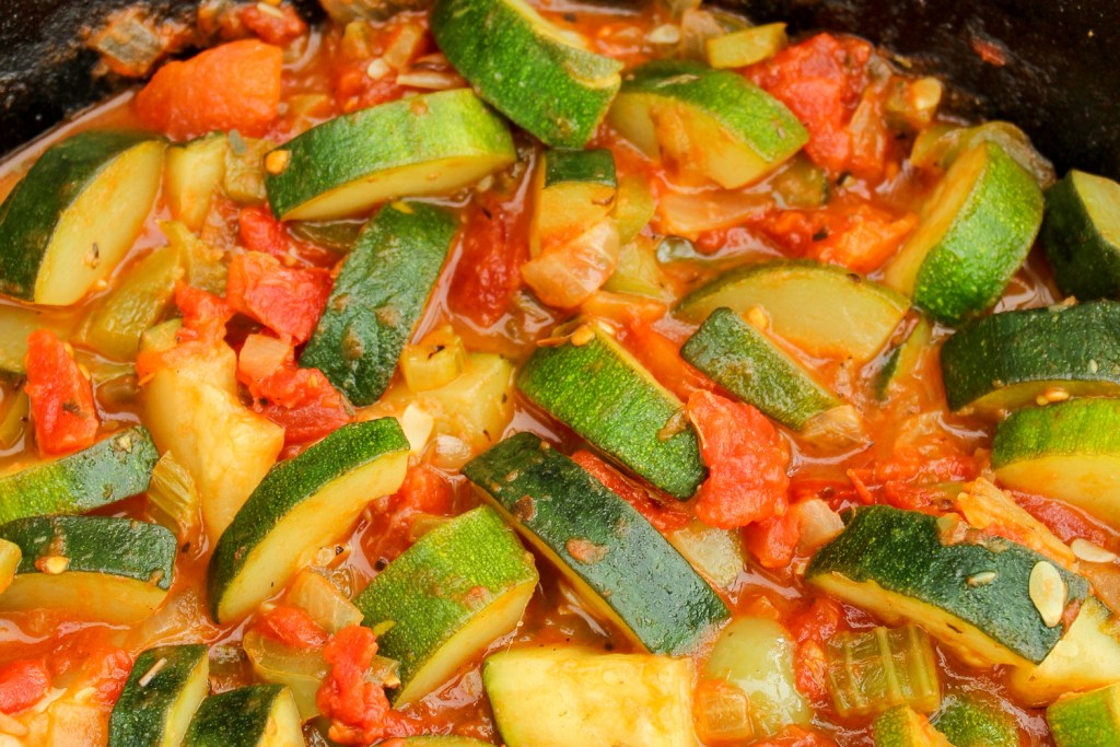 Super close up image of the zucchini, tomatoes, and other vegetables sautéing in a cast iron skillet.
