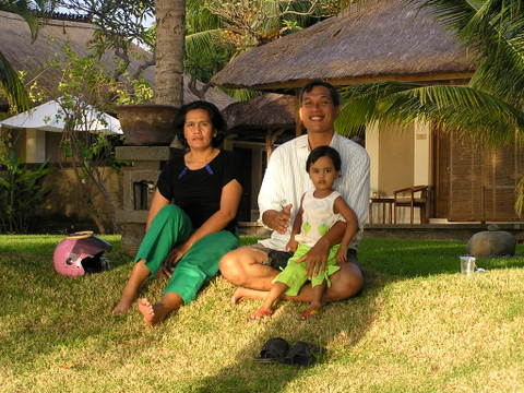 Local family enjoying the sunset from the foreshore at the Puri Bagus resort, Lovina