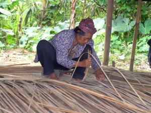 Weaving the traditional split bamboo wall linings that are so often seen in Balinese buildings