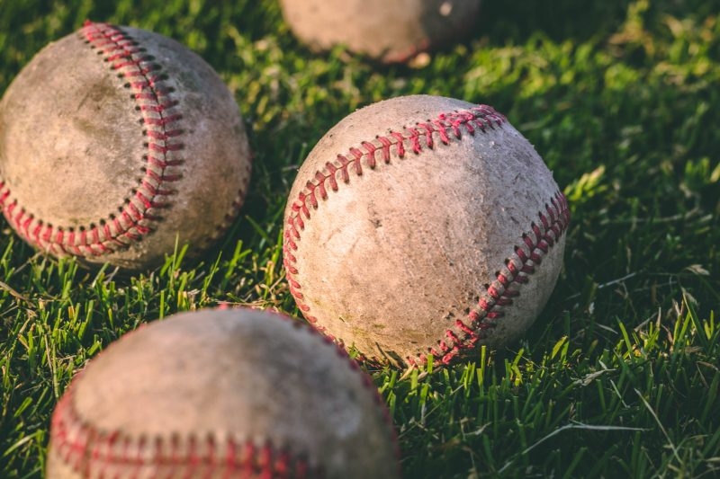 Canva - Close Up Photography of Four Baseballs on Green Lawn Grasses