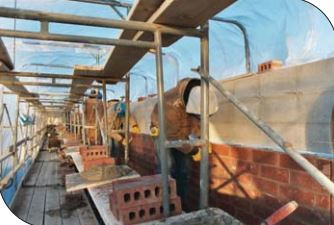 Enclosure and heating of work area to protect the materials, workers and installed masonry from severe cold weather