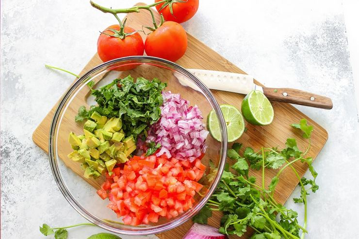A quick and easy recipe for Pico De Gallo (Salsa Fresca) with fresh avocado, tomatoes, red onions, lemon juice and cilantro. Use it as a dip or topping for tacos!