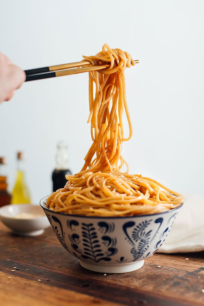 Some chopsticks lifting up messy noodles from a bowl overflowing with hibachi noodles.