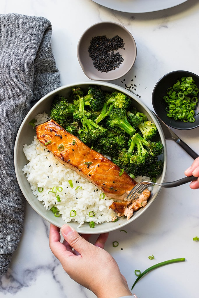 A top down picture of air fryer honey garlic salmon in a bowl with rice and broccoli.