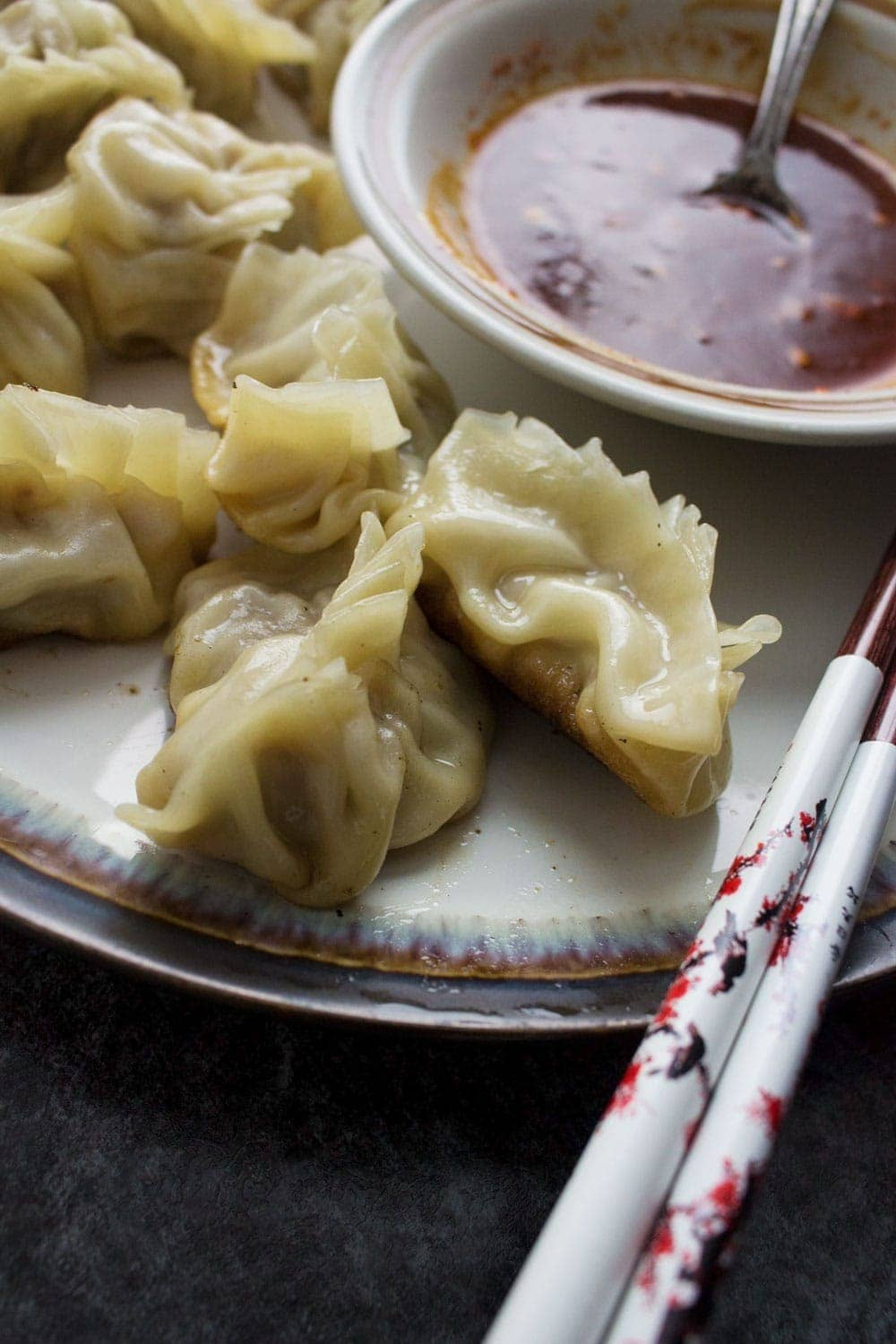 These pork potstickers with a chilli dipping sauce are filling, tasty, & easier than you think! Use premade dumpling wrappers to be ready in under an hour.