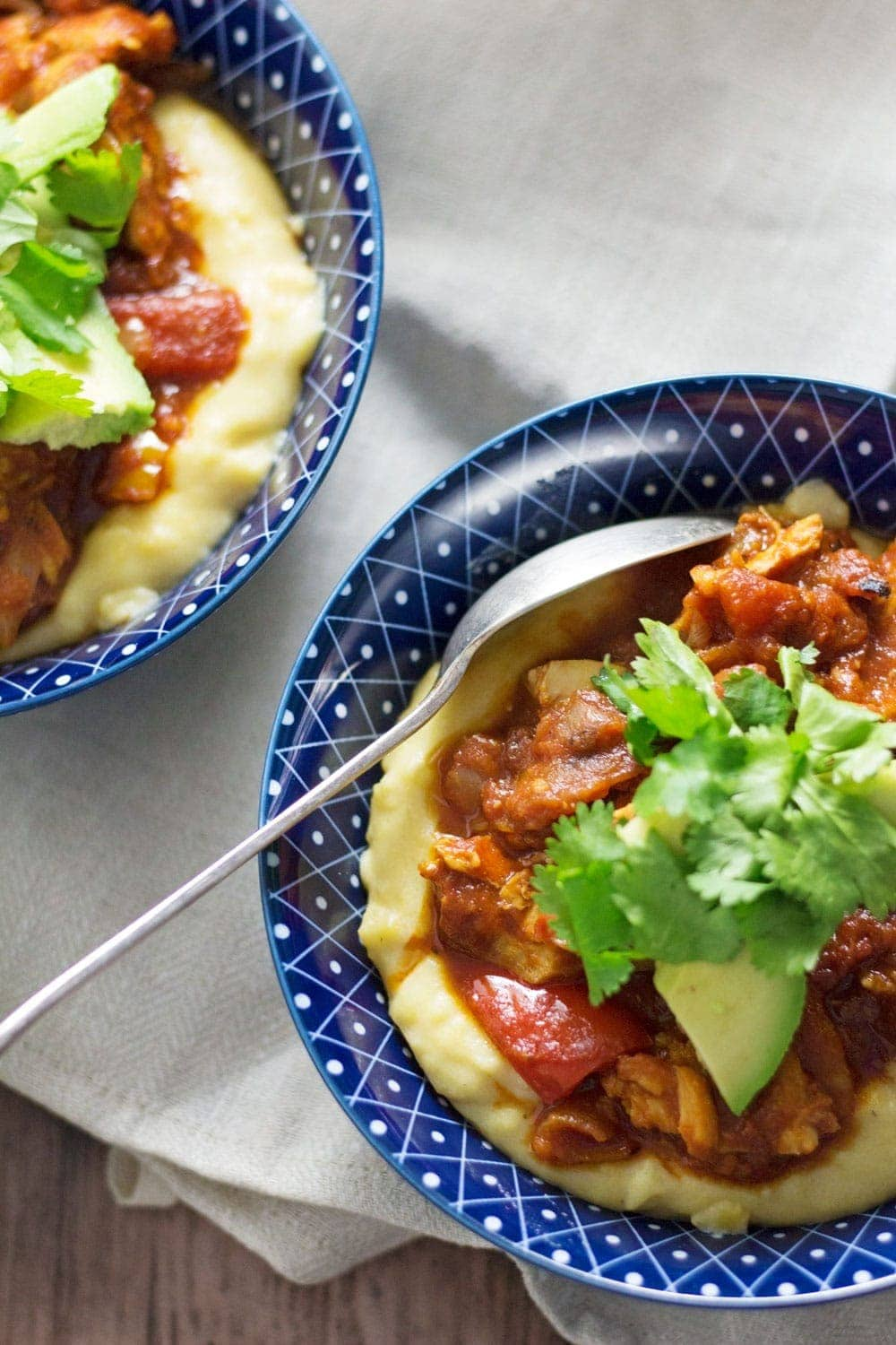These spicy chicken burrito bowls with cheesy polenta are extreme comfort food and surprisingly quick to make! They're the perfect weeknight winter dinner.