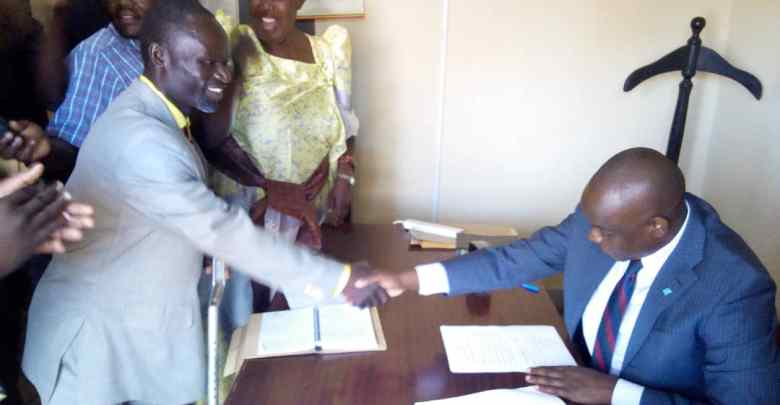 Geoffrey Wandera being congratulated by Umar Kiyimba the district returning officer Busia after winning LC5 elections