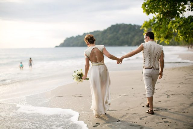 Newlyweds love to walk on the beach and feel the fresh sea breeze around them.