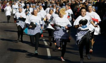 Competitors compete in the Olney 2015 pancake race in Olney, Buckinghamshire in England Tuesday, Feb. 17, 2015. A pancake race has been run in the town since 1445 to mark the start of Lent. (AP Photo/Kirsty Wigglesworth)