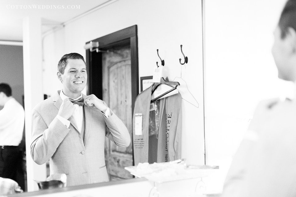 groom adjusting bowtie in mirror