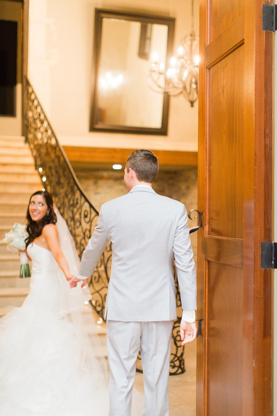 bride leading groom through doors cute
