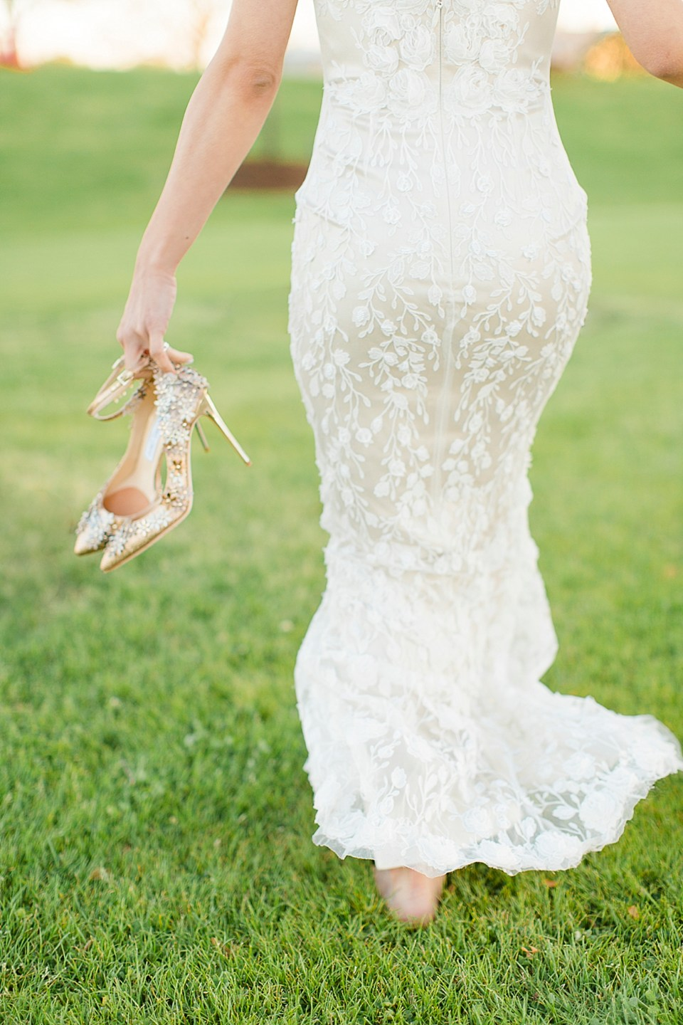 bride walking with shoes in hand