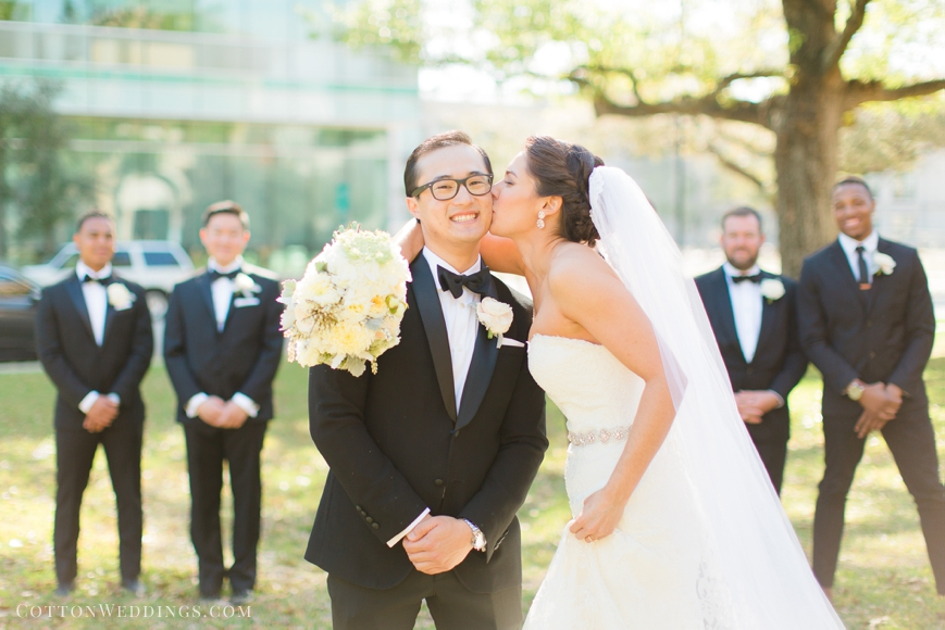 bride kissing groom on cheek with bridal party