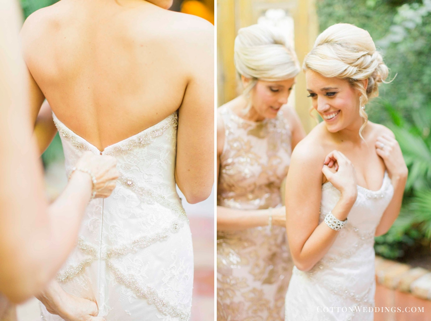 mother putting bride in her dress