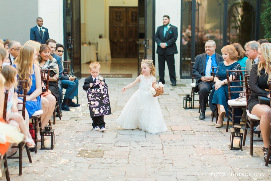 cute ring bearer and flower girl walking down the aisle with sign