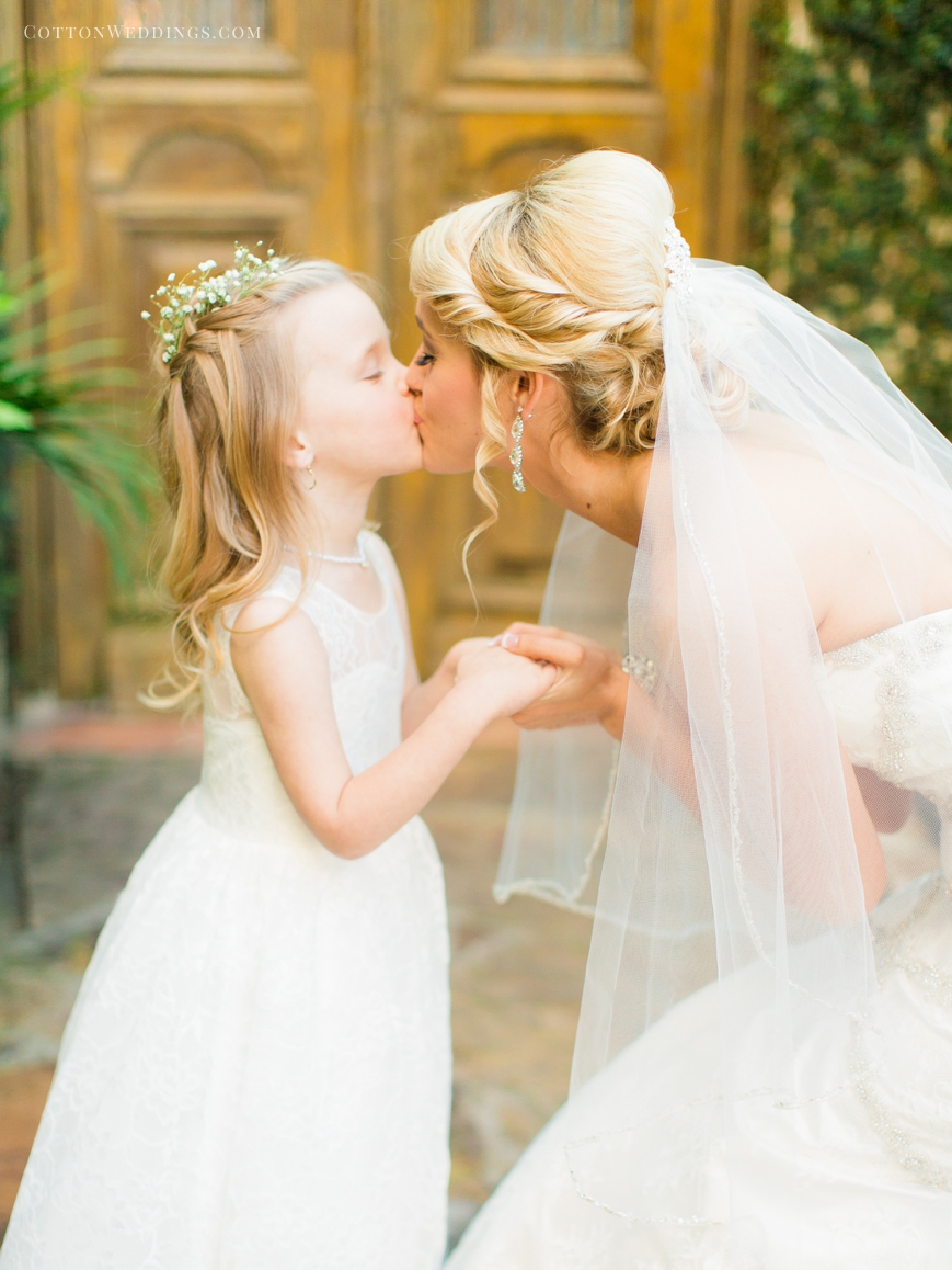 adorable flower girl kissing bride