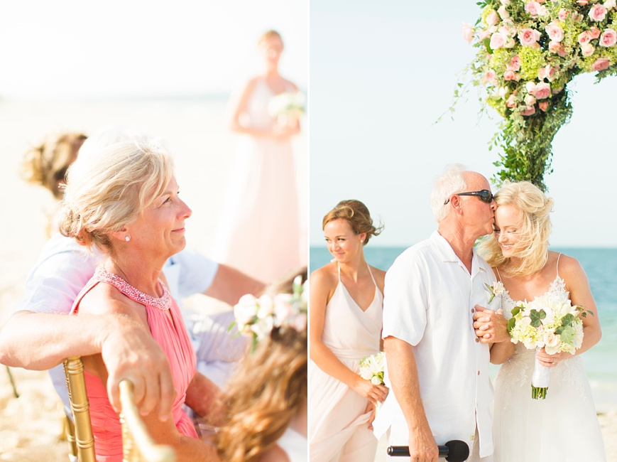 father kissing bride on the forehead during beach wedding