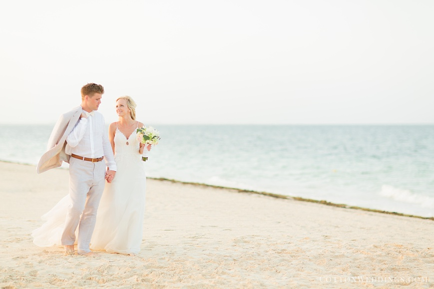 beautiful bride and groom walking on beach