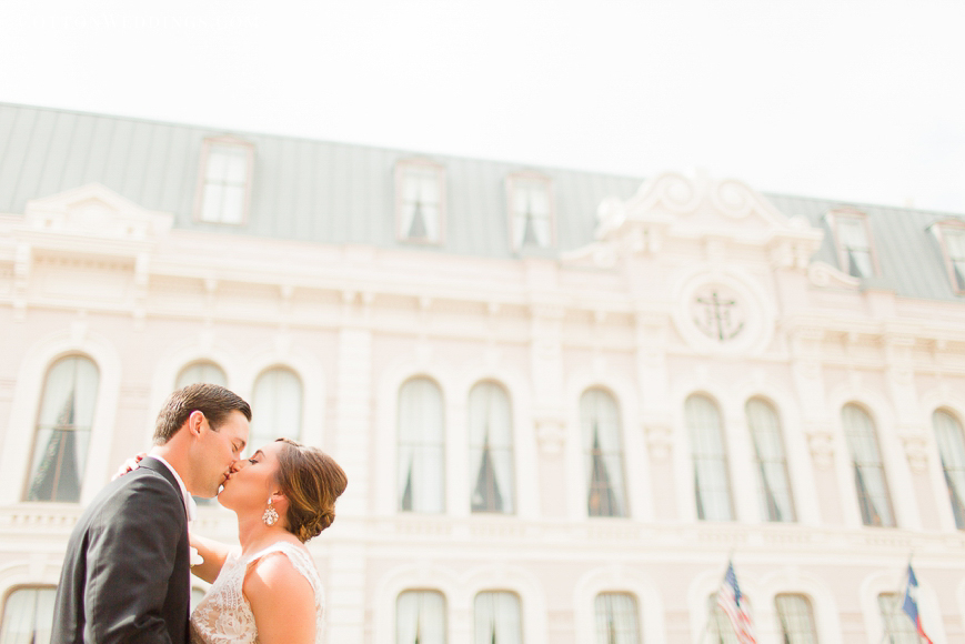 happy bride and groom kissing in front of tremont house galveston